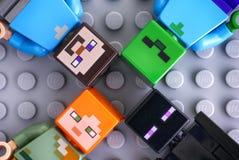 Cuatro minifigures de Lego Minecraft en fondo gris foto de archivo