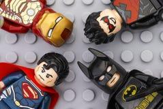 Cuatro minifigures de Lego Super Heroes en placa de base gris Imagenes de archivo