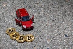 Cuatro monedas de oro de Bitcoin cerca del primer de lujo rojo del coche de la cruce en el asfalto texturizan el fondo con un cop imagen de archivo