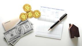 Cuatro monedas de oro del bitcoin, moneda crypto digital, al lado a una lista personal de costos y de gastos fotografía de archivo libre de regalías
