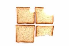 Cuatro mordeduras de pan de la tostada en el fondo blanco foto de archivo