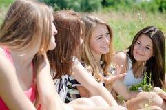 Cuatro muchachas adolescentes felices que comparten secretos Fotografía de archivo libre de regalías