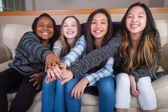 Cuatro muchachas culturaly diversas que llevan a cabo las manos en la unidad Imágenes de archivo libres de regalías