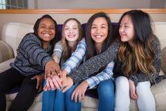 Cuatro muchachas culturaly diversas que llevan a cabo las manos en la unidad Foto de archivo libre de regalías