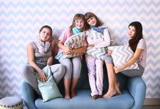 Cuatro muchachas en partido de pijama con las almohadas Fotografía de archivo libre de regalías