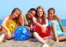 Cuatro muchachas en una playa Foto de archivo