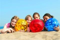 Cuatro muchachas en una playa Imagen de archivo libre de regalías
