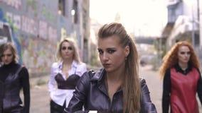 Cuatro muchachas extrañas del cuero de la moda y motocicleta negra Mujeres punkyes jovenes en escena urbana de la pintada almacen de metraje de vídeo