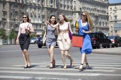 Cuatro muchachas hermosas de la moda que caminan en la calle Imagen de archivo