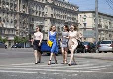 Cuatro muchachas hermosas de la moda que caminan en la calle Fotos de archivo