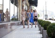 Cuatro muchachas hermosas de la moda que caminan en la calle Foto de archivo