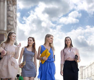 Cuatro muchachas hermosas de la moda que caminan en la calle Imágenes de archivo libres de regalías