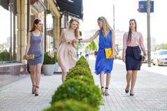 Cuatro muchachas hermosas de la moda que caminan en la calle Fotografía de archivo
