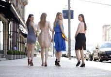 Cuatro muchachas hermosas de la moda que caminan en la calle Fotos de archivo libres de regalías