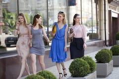 Cuatro muchachas hermosas de la moda que caminan en la calle Fotografía de archivo libre de regalías