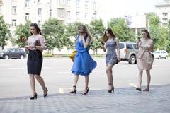 Cuatro muchachas hermosas de la moda que caminan en la calle Foto de archivo libre de regalías