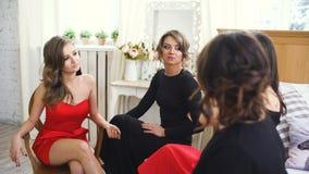 Cuatro muchachas hermosas tienen negociaciones del chisme mientras que se sientan en las mujeres de la cama que se divierten ríen almacen de video