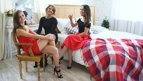 Cuatro muchachas hermosas tienen negociaciones del chisme mientras que se sientan en las mujeres de la cama que se divierten ríen metrajes