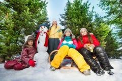 Cuatro muchachas hicieron el muñeco de nieve divertido en el bosque Imágenes de archivo libres de regalías