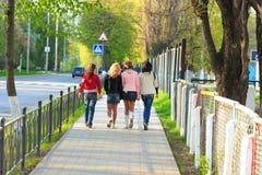 Cuatro muchachas que recorren a lo largo de la calle Fotos de archivo libres de regalías