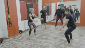 Cuatro muchachos jovenes activos y una muchacha que resuelve su cuerpo en una clase apta del gimnasio de la cruz haciendo serie d metrajes