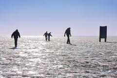 Cuatro muchachos que hacen una caminata cuidadosa en un lago congelado Imagen de archivo