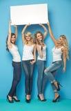 Cuatro mujeres alegres que llevan al tablero vacío imágenes de archivo libres de regalías