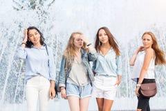 Cuatro mujeres atractivas en ropa del verano se colocan cerca de la fuente en un día caliente Un grupo de mujeres atractivas foto de archivo libre de regalías