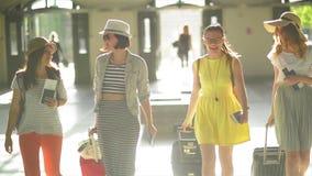 Cuatro mujeres bonitas en ropa brillante del verano con los documentos, los boletos, y las maletas grandes en manos van a metrajes