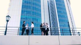 Cuatro mujeres de negocios y dos hombres de negocios que tienen discusión al aire libre en un día de verano almacen de metraje de vídeo