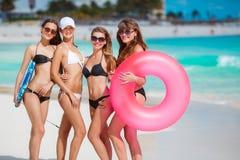Cuatro mujeres en bikinis con la cuerda de salvamento cerca del océano Foto de archivo libre de regalías