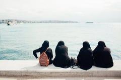 Cuatro mujeres en burka se sientan con sus partes posteriores y miran el mar imágenes de archivo libres de regalías