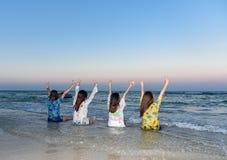 Cuatro mujeres eran amigos, sentados cómodamente y aumentaron sus manos en la playa fotos de archivo