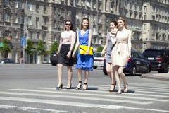 Cuatro mujeres hermosas de la moda que caminan en la calle Fotos de archivo libres de regalías