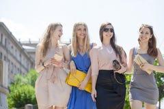 Cuatro mujeres hermosas de la moda que caminan en la calle Imagenes de archivo
