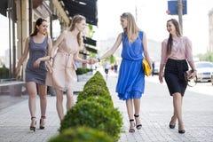 Cuatro mujeres hermosas de la moda que caminan en la calle Foto de archivo libre de regalías
