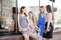Cuatro mujeres hermosas de la moda que caminan en la calle Foto de archivo