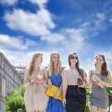 Cuatro mujeres hermosas de la moda que caminan en la calle Imagen de archivo