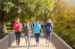 Cuatro mujeres jovenes que activan sobre el puente Imagen de archivo