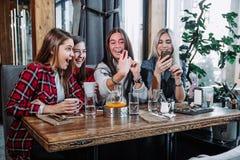 Cuatro mujeres jovenes que se sientan en café usando el teléfono elegante y que tienen conversación divertida fotografía de archivo