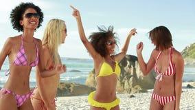 Cuatro mujeres que llevan las gafas de sol que van de fiesta en sus bikinis almacen de video