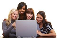 Cuatro mujeres que miran una computadora portátil imagen de archivo