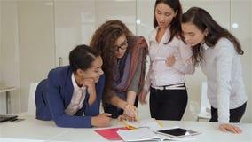 Cuatro mujeres se colocan cerca de la tabla con los papeles y la tableta almacen de metraje de vídeo