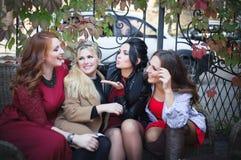 Cuatro mujeres se divierten que hablan cuando se encuentran imagenes de archivo
