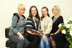 Cuatro mujeres se sientan en el sofá de cuero negro Imágenes de archivo libres de regalías