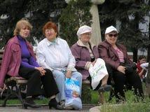 Cuatro mujeres se sientan en un banco Fotos de archivo libres de regalías