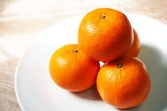 Cuatro naranjas en la placa imagen de archivo