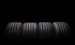 Cuatro neumáticos de goma del automóvil aislados en negro Fotografía de archivo