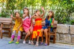 Cuatro niñas que se sientan en el banco y las burbujas que soplan Imágenes de archivo libres de regalías