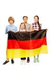Cuatro niños adolescentes multiétnicos que sostienen la bandera alemana Foto de archivo